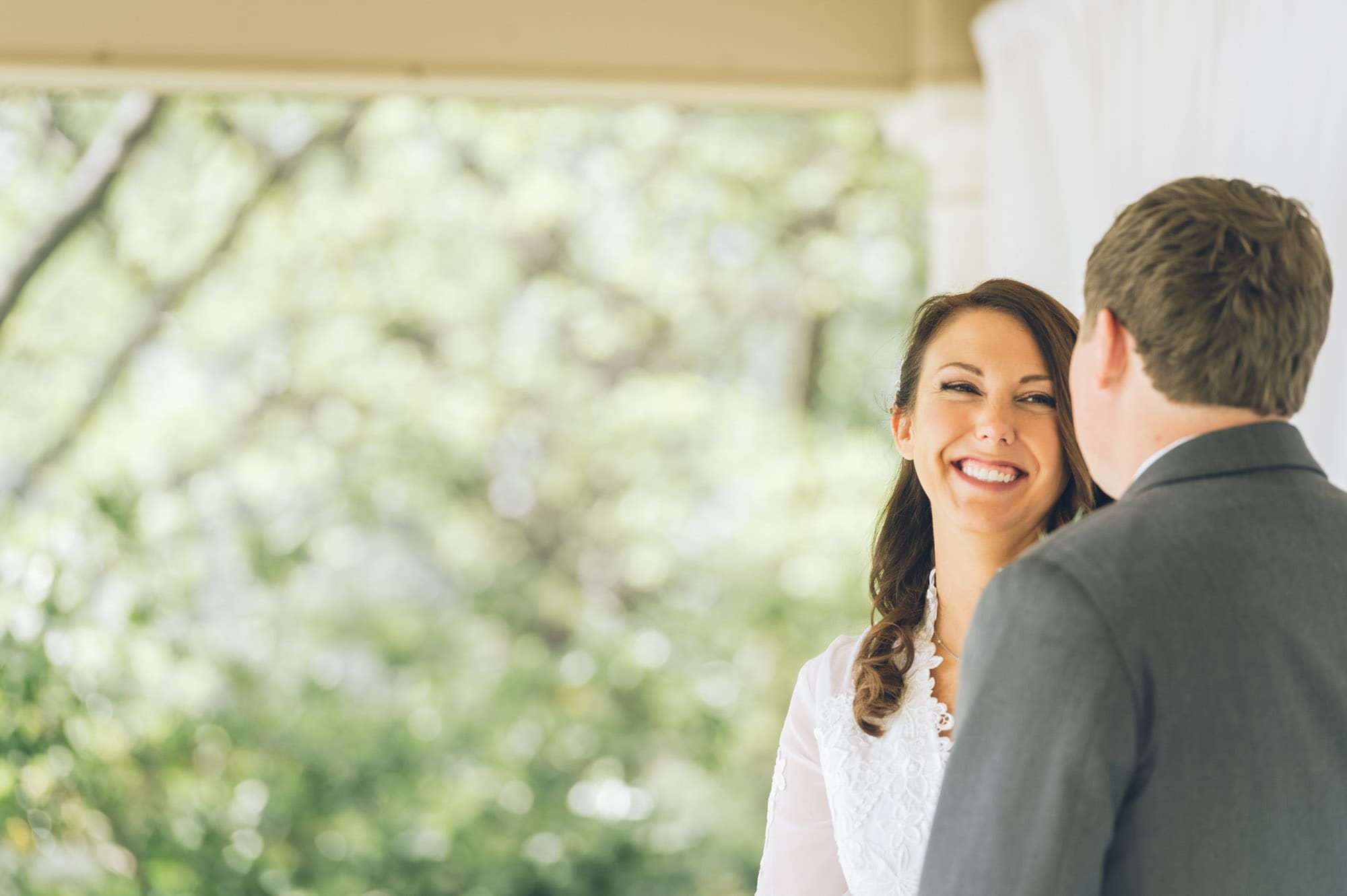 newlywed woman smiling staring at her her groom, photographed by Eivan's in Dallas