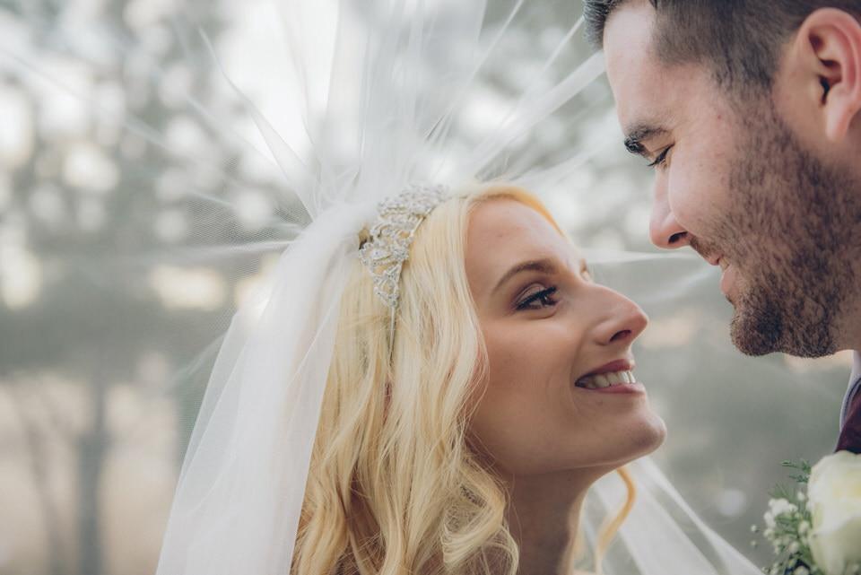 newlyweds under brides veil, denver wedding photographer availability