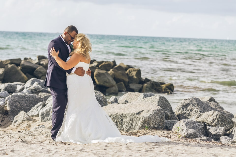 newlyweds kissing near beach rocks, miami wedding photographer packages and pricing