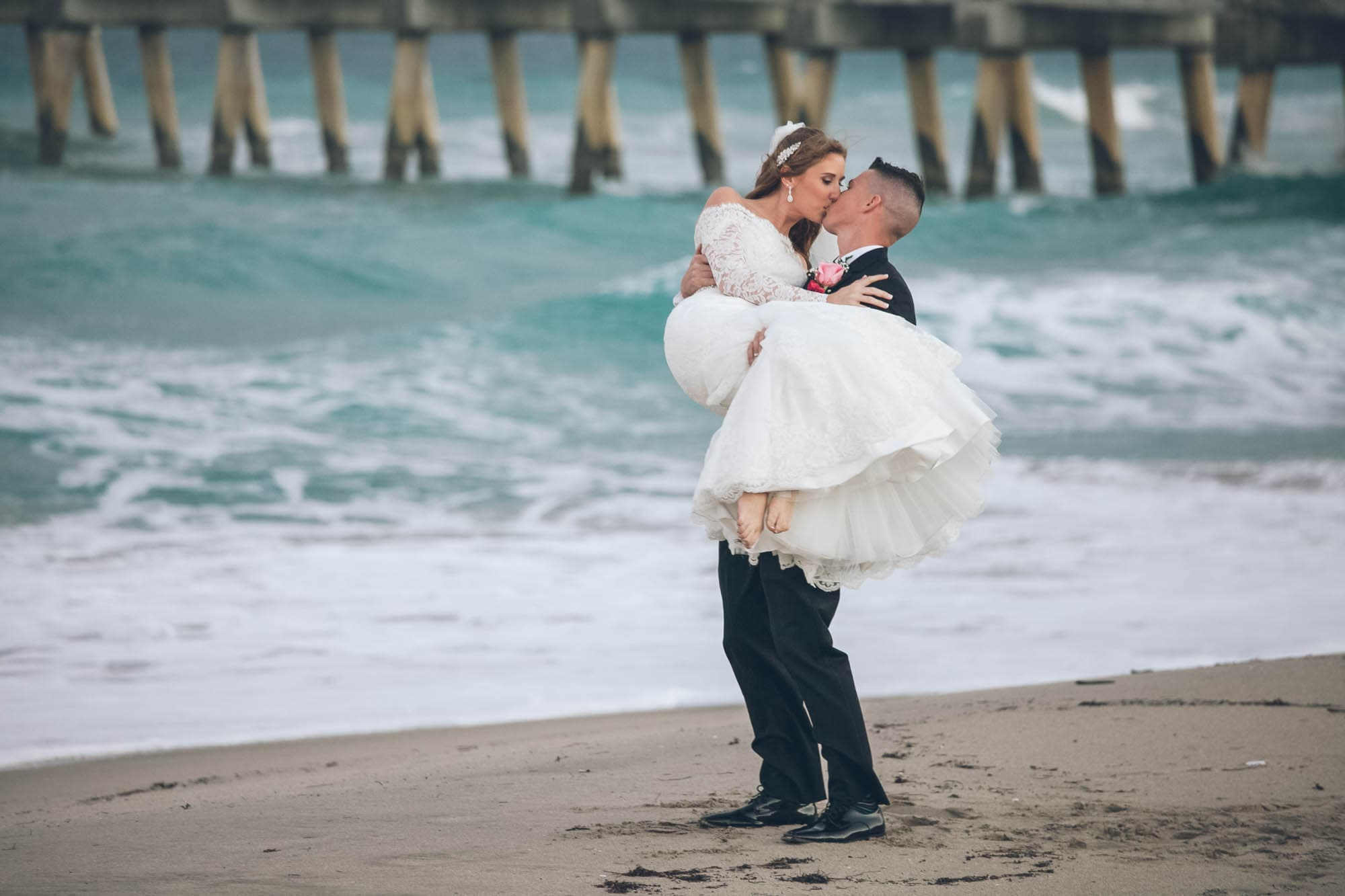 newlywed groom kissing bride at a beach, photographed by Eivan's in Miami