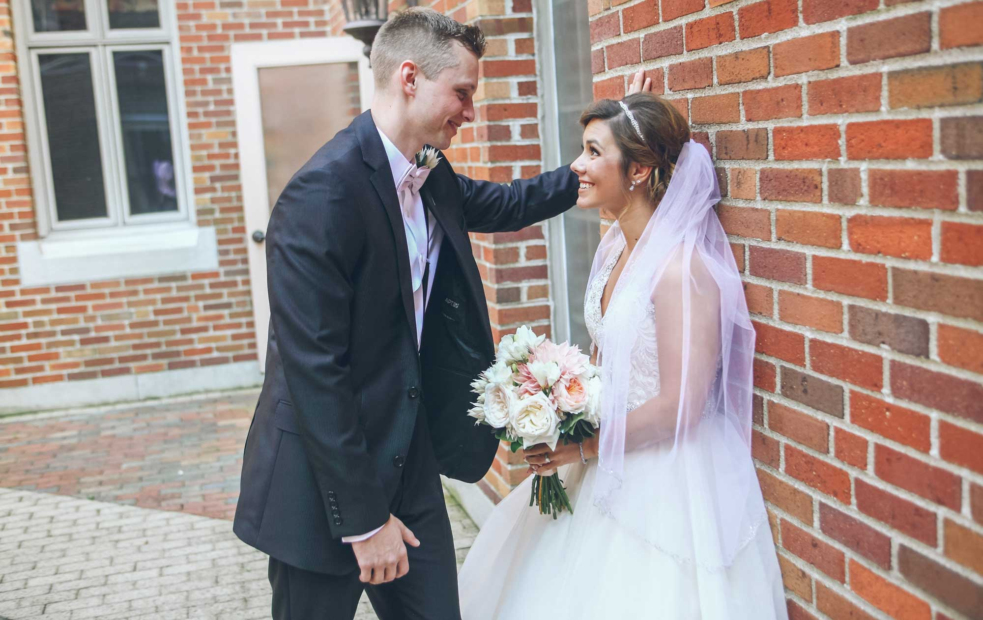 newlyweds posing in front of a brick wall, photographed by Eivan's in Cleveland