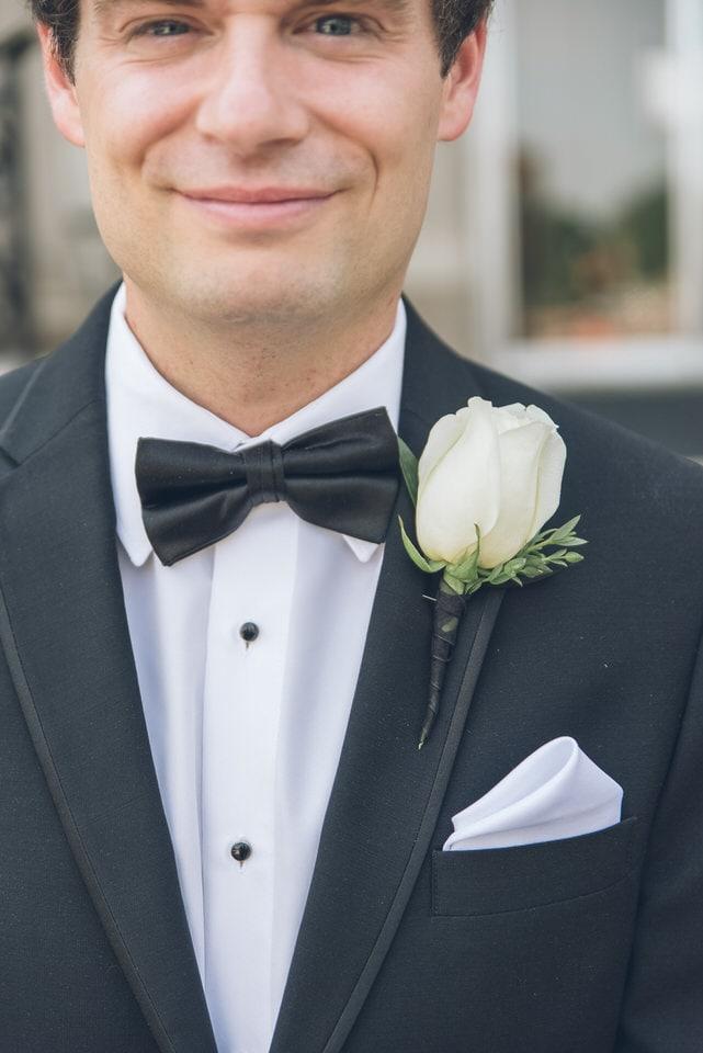 man in black suit jacket holding white rose