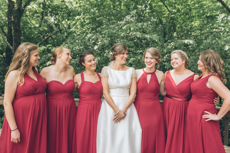 six women in red and white dresses standing near green trees during daytime