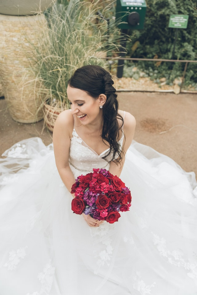woman in white tube dress holding red bouquet of flowers