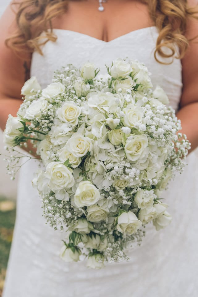 white rose bouquet on persons hand