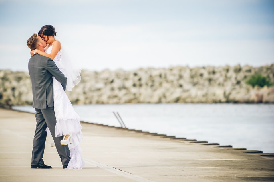 man and woman kissing on gray concrete road during daytime