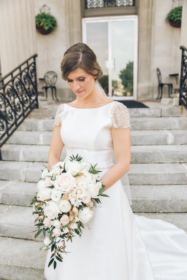 woman in white floral lace dress holding bouquet of white roses
