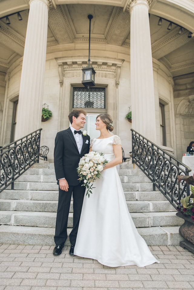 man in black suit and woman in white wedding dress walking on gray concrete stairs