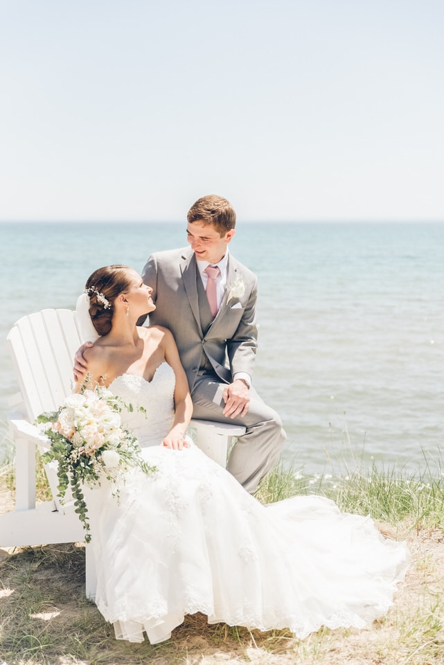 man in gray suit and woman in white wedding dress kissing on beach during daytime