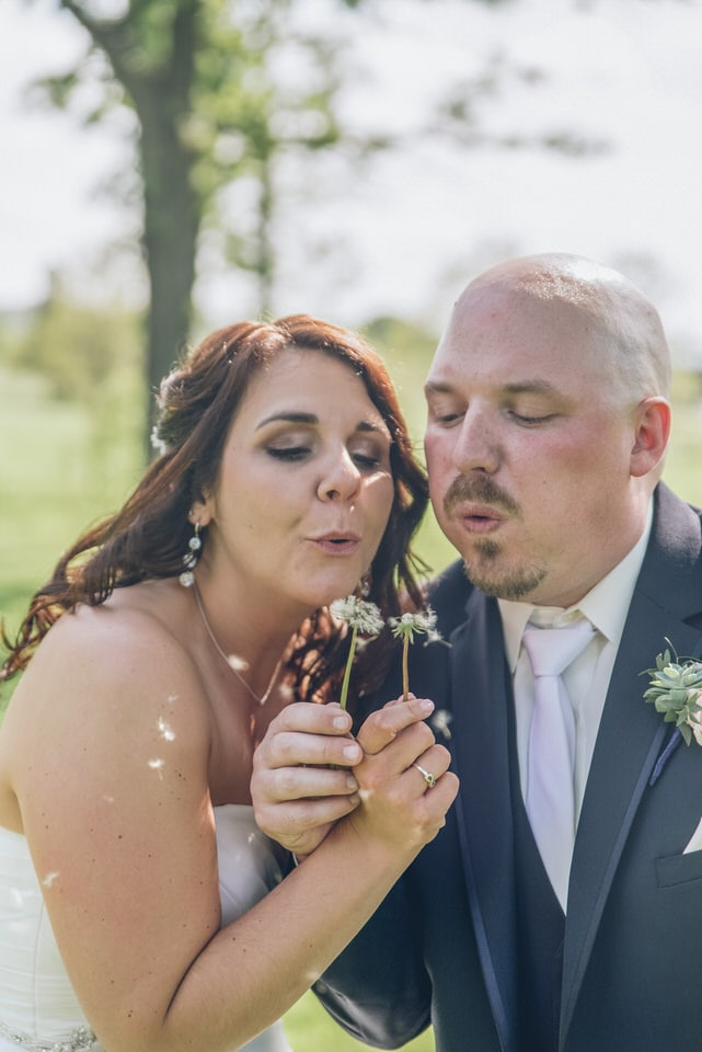 man in black suit kissing woman in white tube dress
