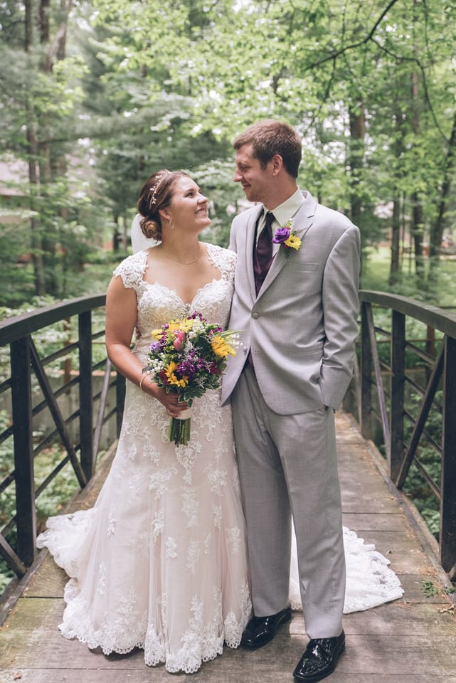 man in gray suit and woman in white wedding dress holding bouquet of flowers