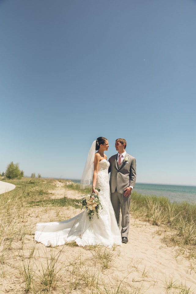 man and woman in wedding dress walking on brown sand near body of water during daytime