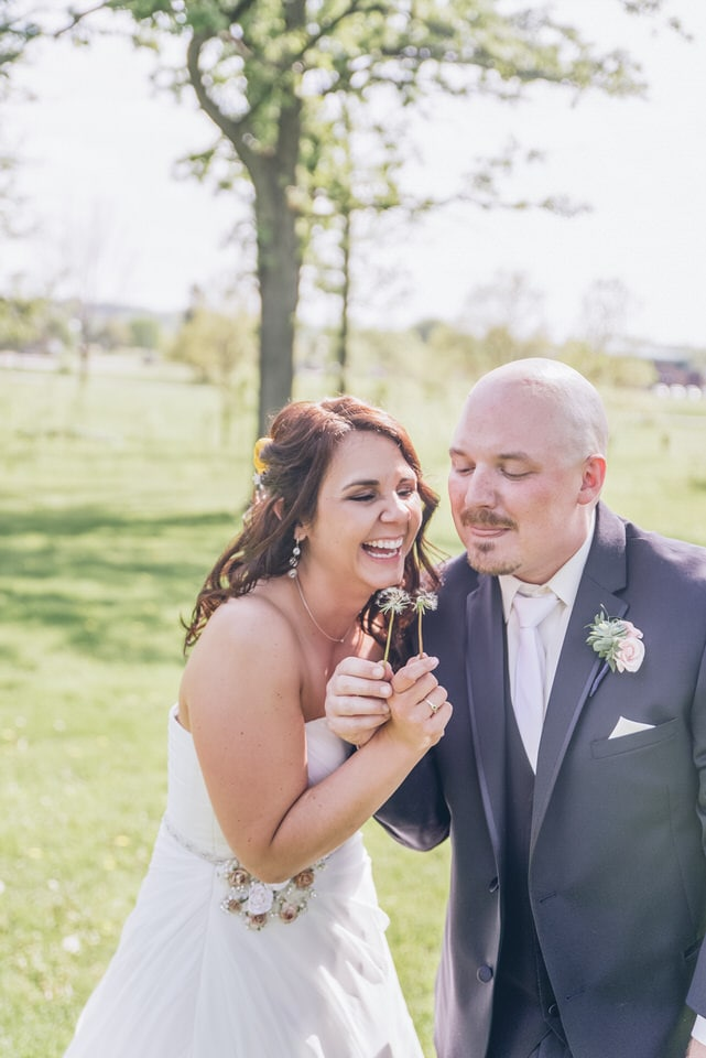 bride laughing over grooms shoulder, milwaukee wedding photographer packages and pricing