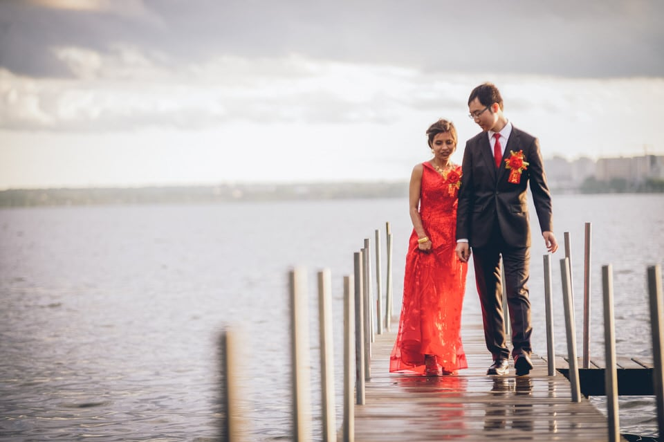 man in black suit and woman in red dress standing on sea dock during daytime