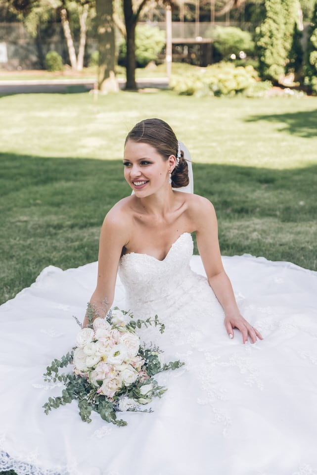 woman in white tube dress holding white flower bouquet