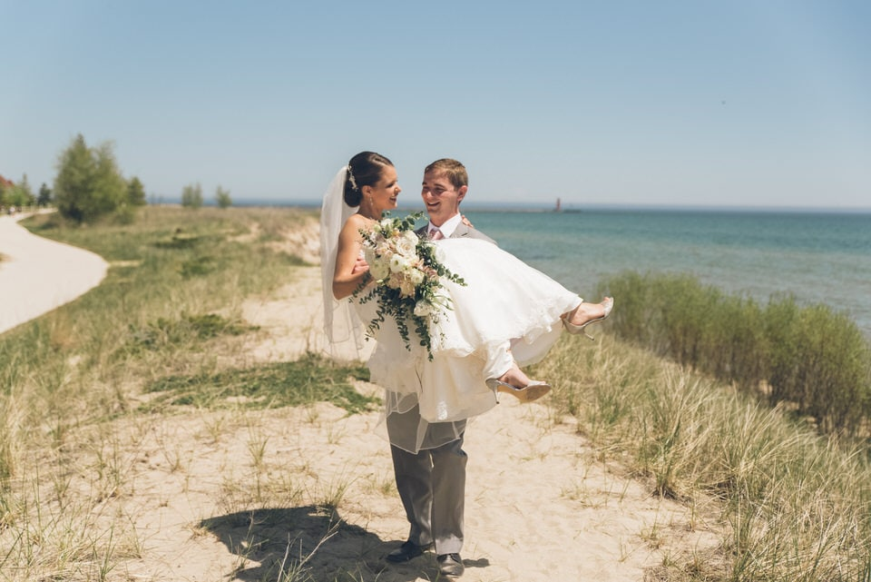 man and woman holding bouquet of flowers standing on brown sand near body of water during