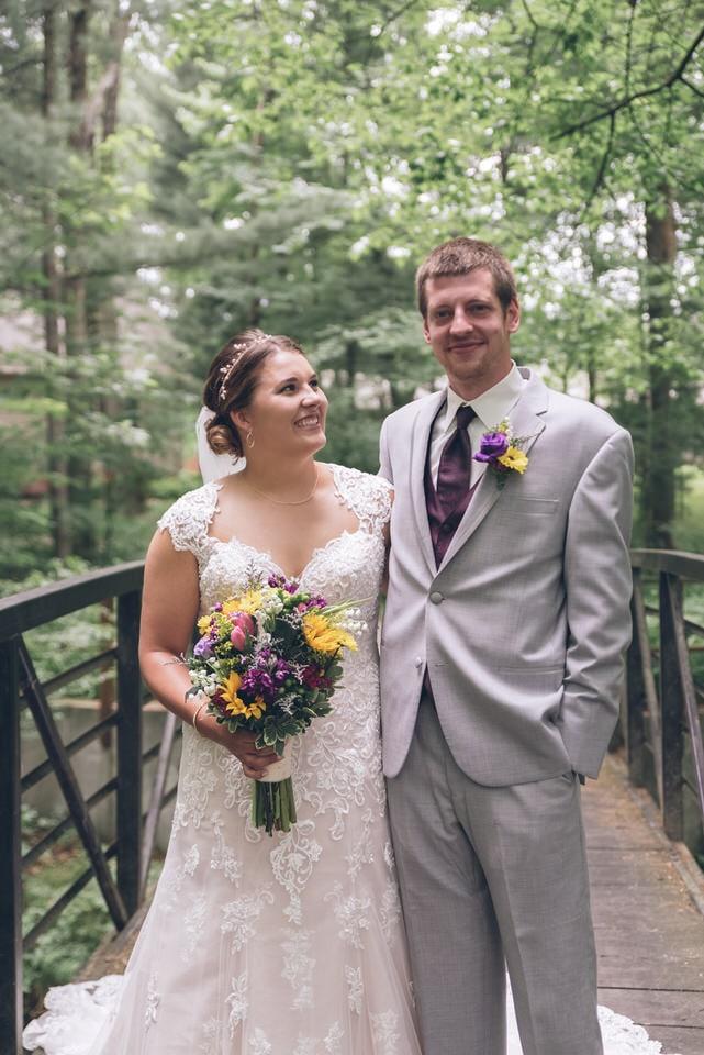 man in gray suit standing beside woman in white wedding dress