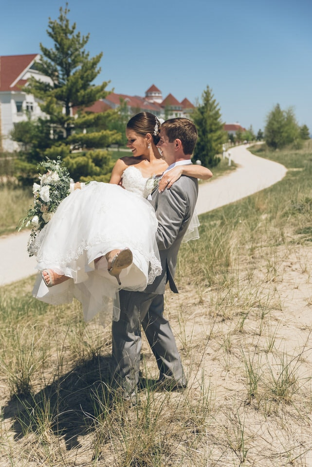 man in brown pants carrying woman in white wedding dress during daytime