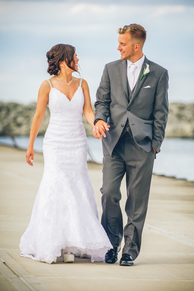 newlyweds strolling and holding hands, milwaukee wedding photographer availability