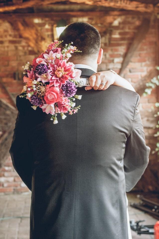 man in gray dress shirt hugging woman in white dress