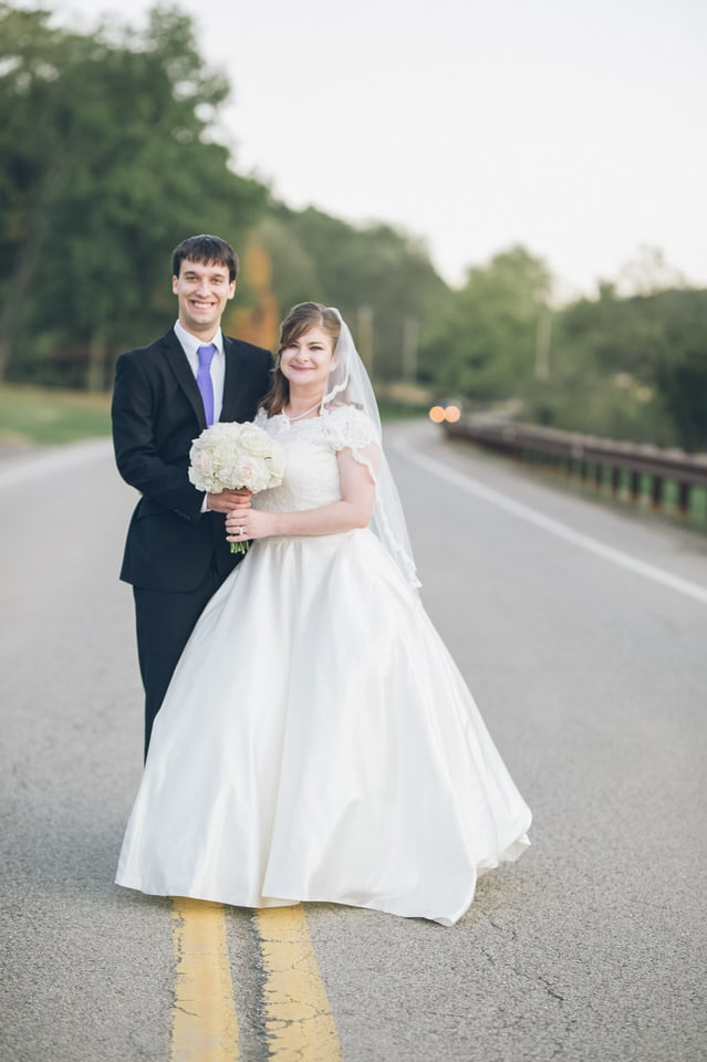 man in black suit and woman in white wedding dress holding bouquet of flowers walking on on on on on