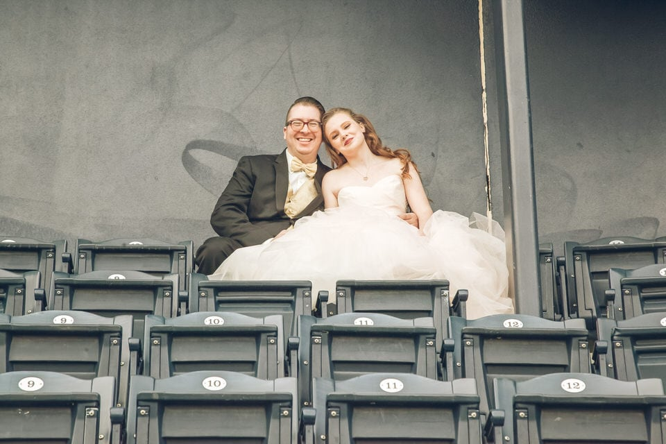 woman in white wedding gown sitting beside man in black suit
