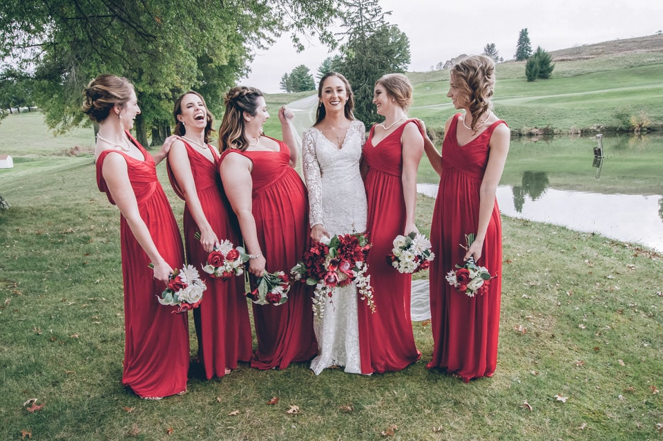 six women in red dresses standing on green grass field during daytime