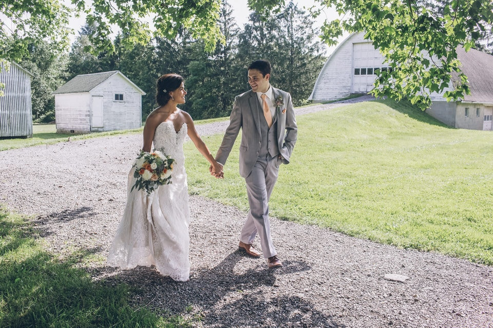 man in gray suit holding hands with woman in white wedding dress walking on pathway during