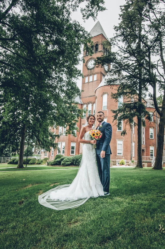 bride and groom standing on green grass field near brown concrete building during daytime