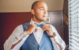 man in a suit fixing his bow tie