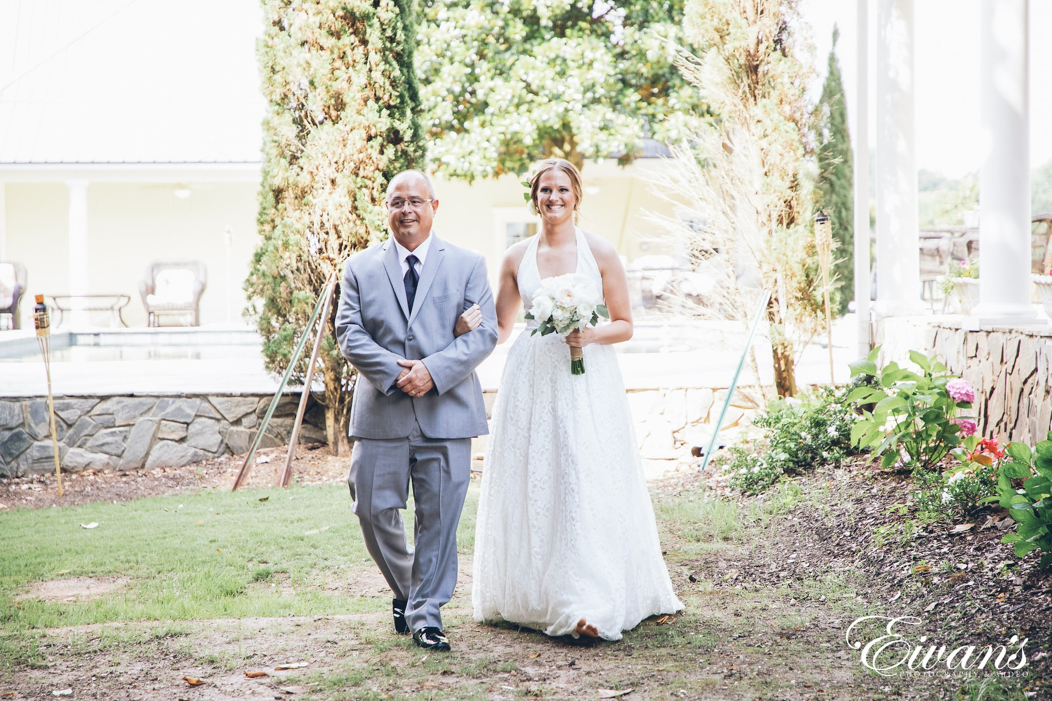 woman in a white dress walking down the aisle with her father