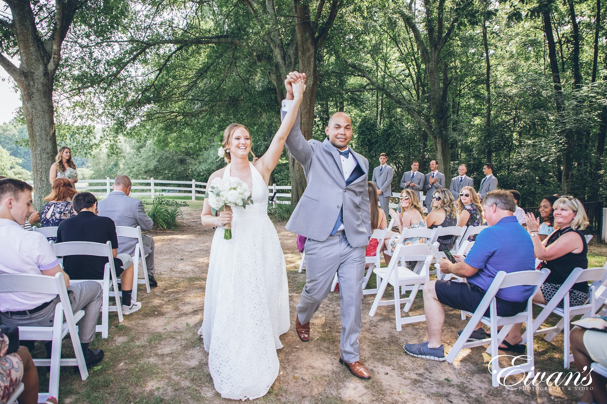 man and woman holding hands up while walking down the aisle