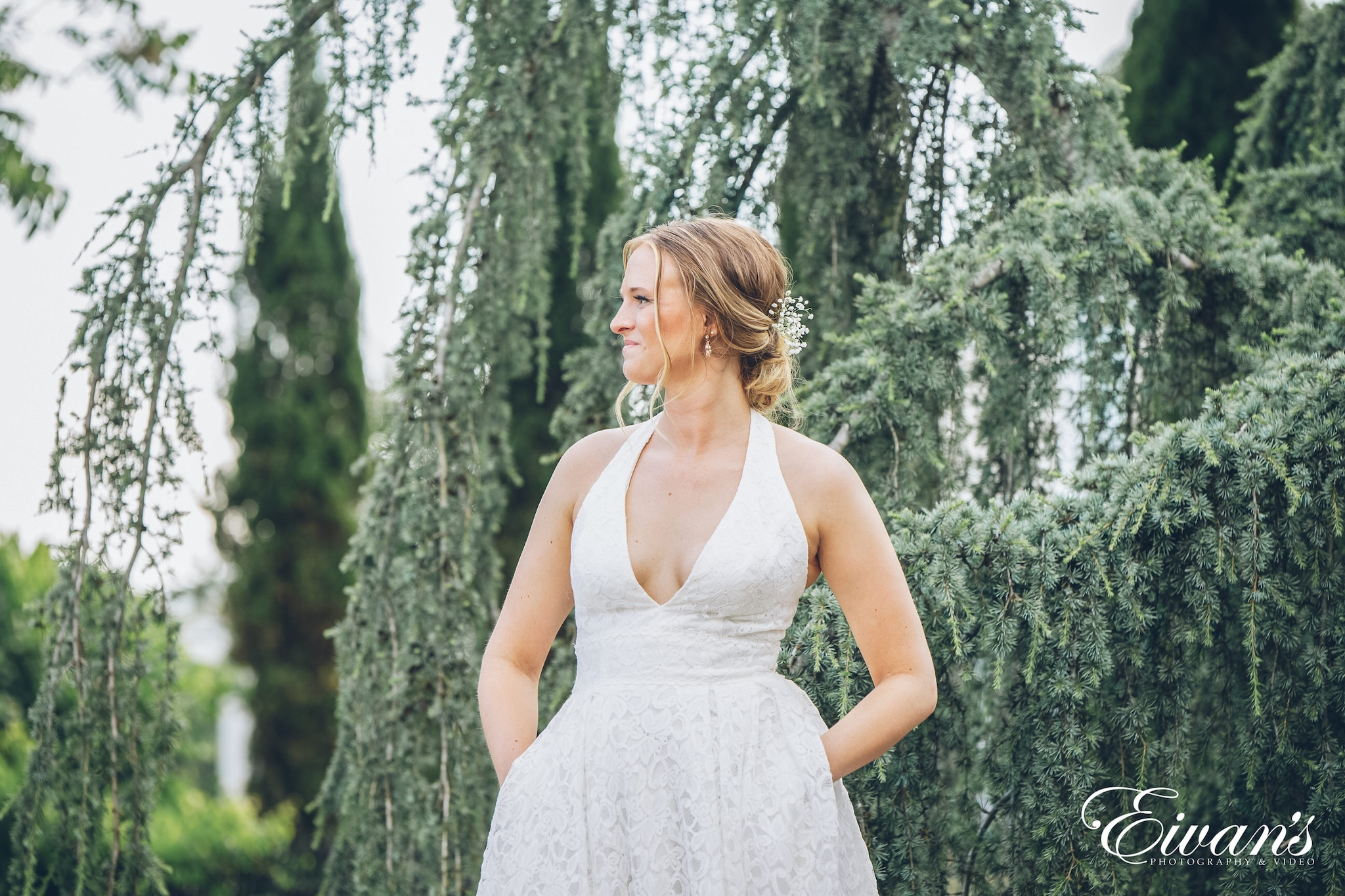 bride wearing a white dress posed in front of trees
