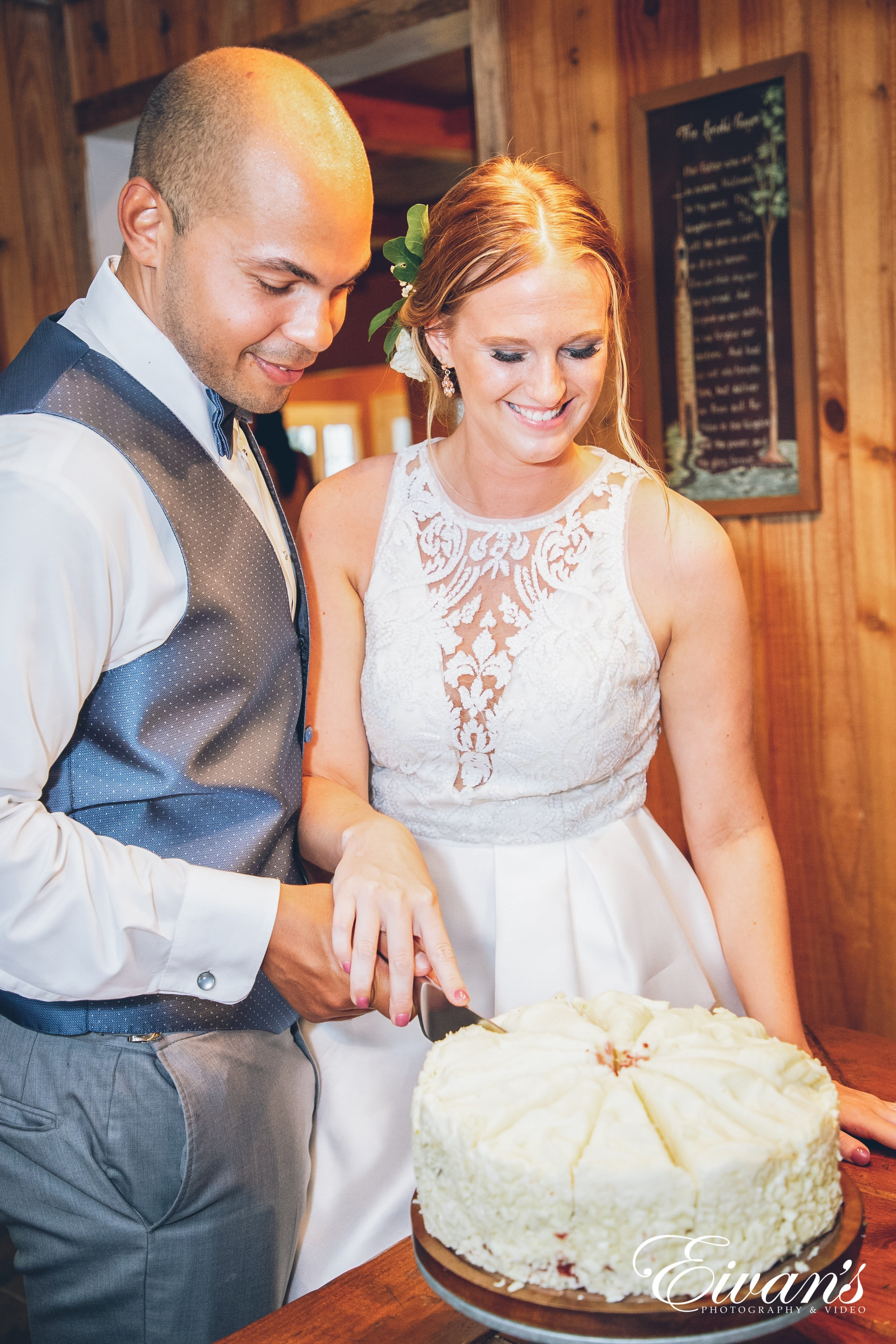 man and woman in a white dress cutting a cake