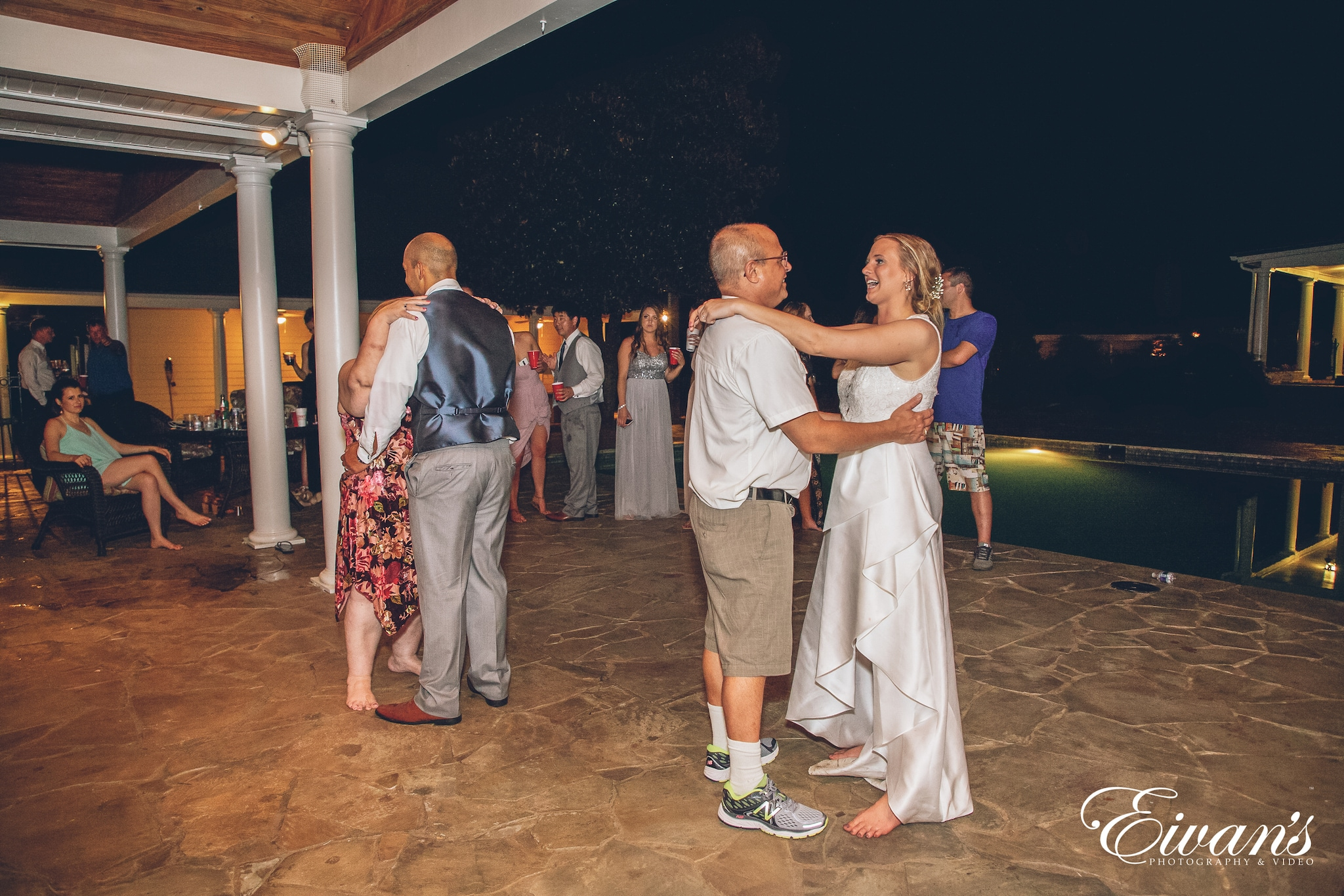bride in a white dress dancing with her father