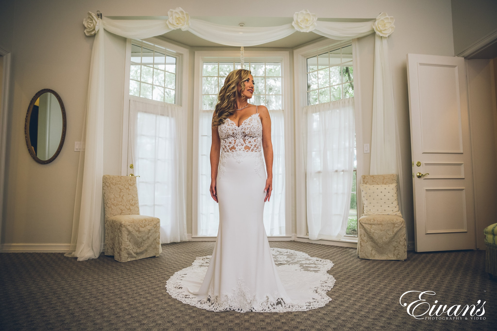 woman in white floral wedding dress standing on gray carpet