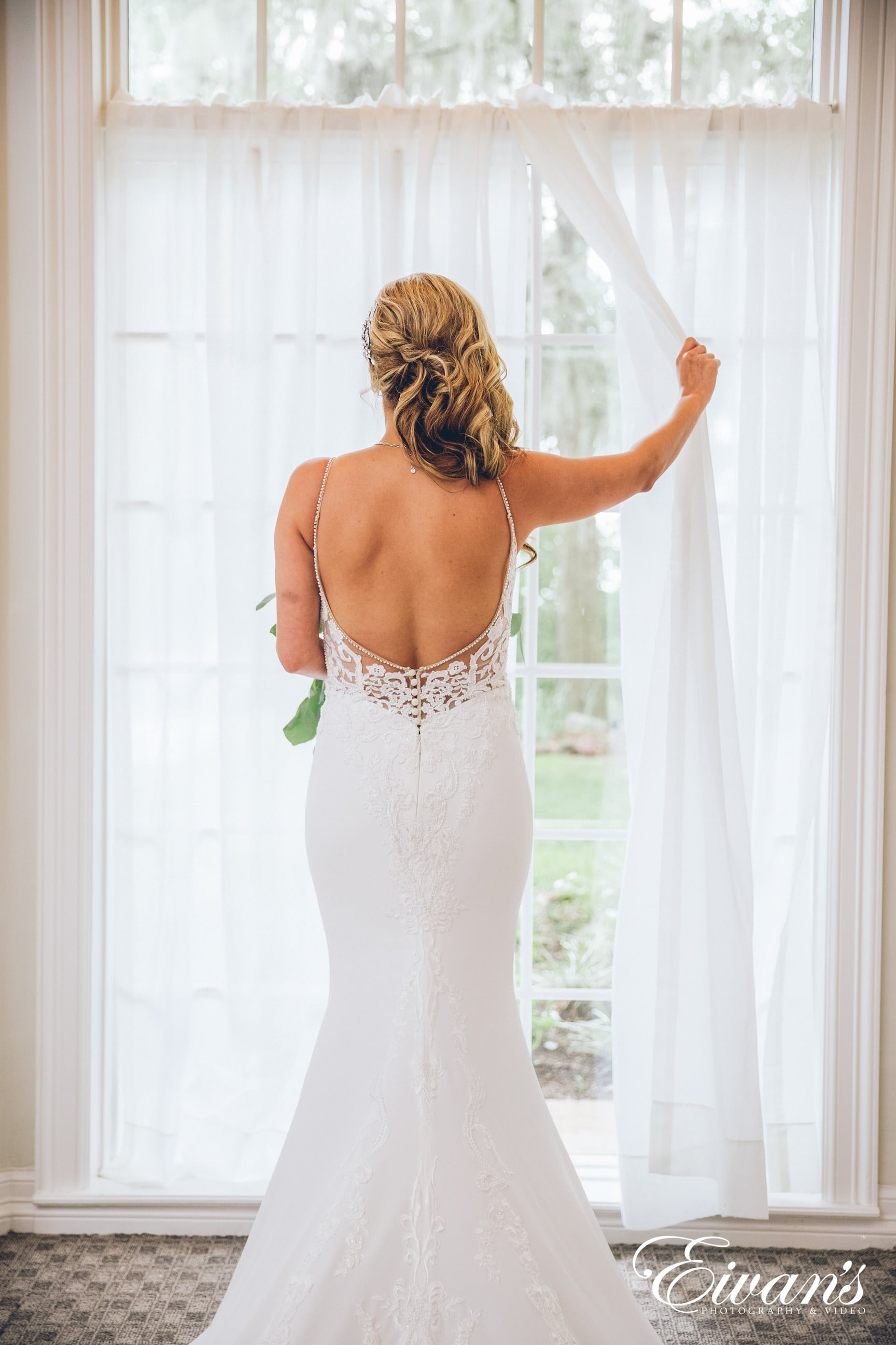 woman in white floral spaghetti strap dress standing near white window curtain