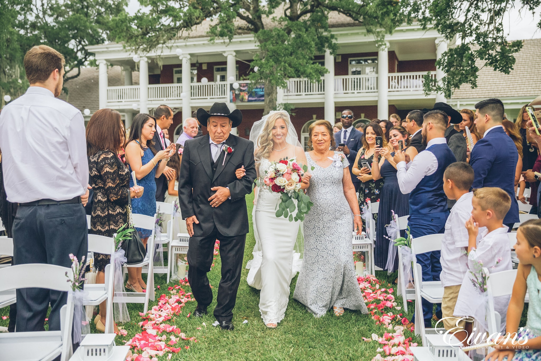 woman in white wedding gown standing between man in black suit and woman in white wedding