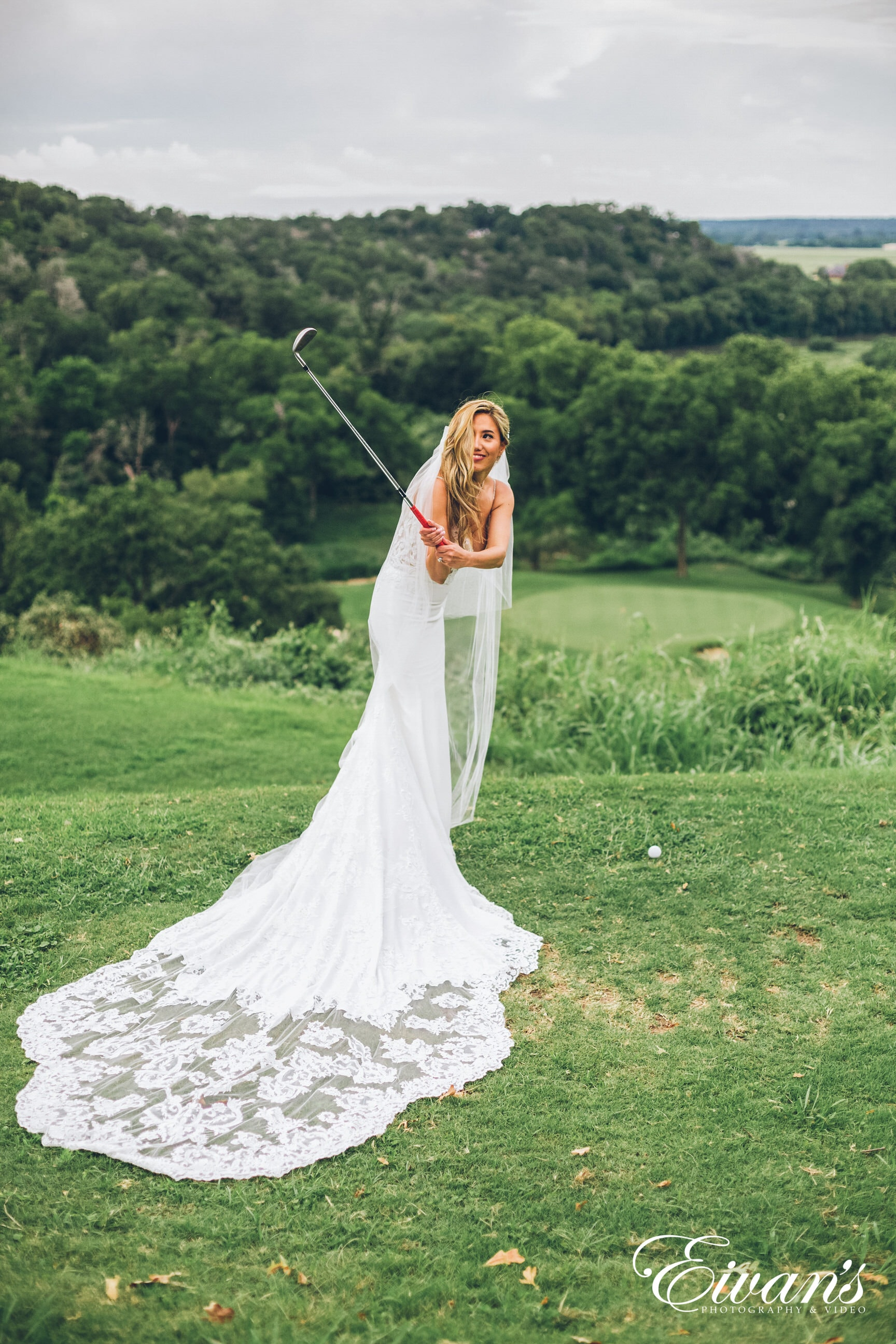 woman in white dress holding stick standing on green grass field during daytime