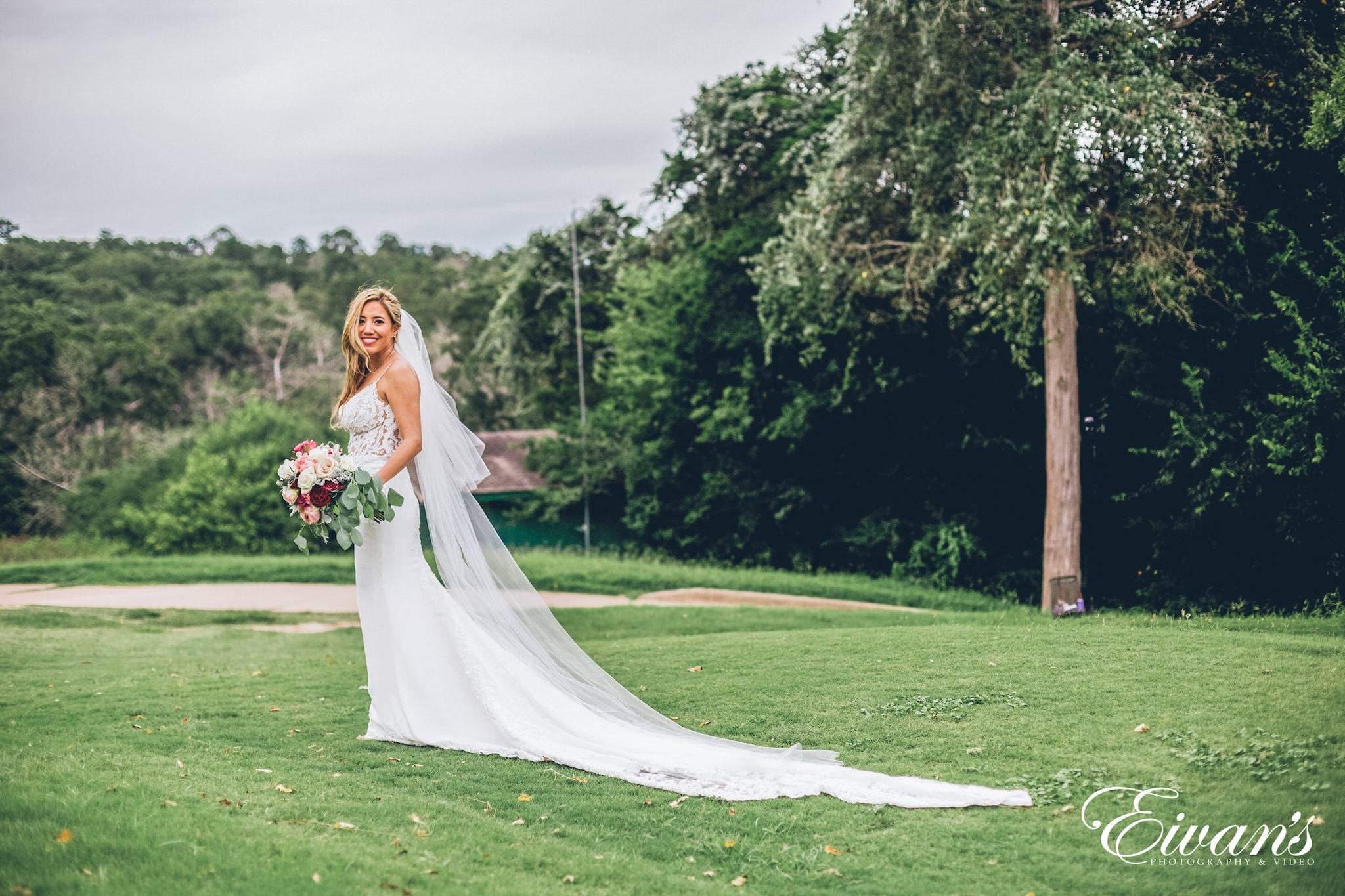 woman in white wedding dress standing on green grass field during daytime