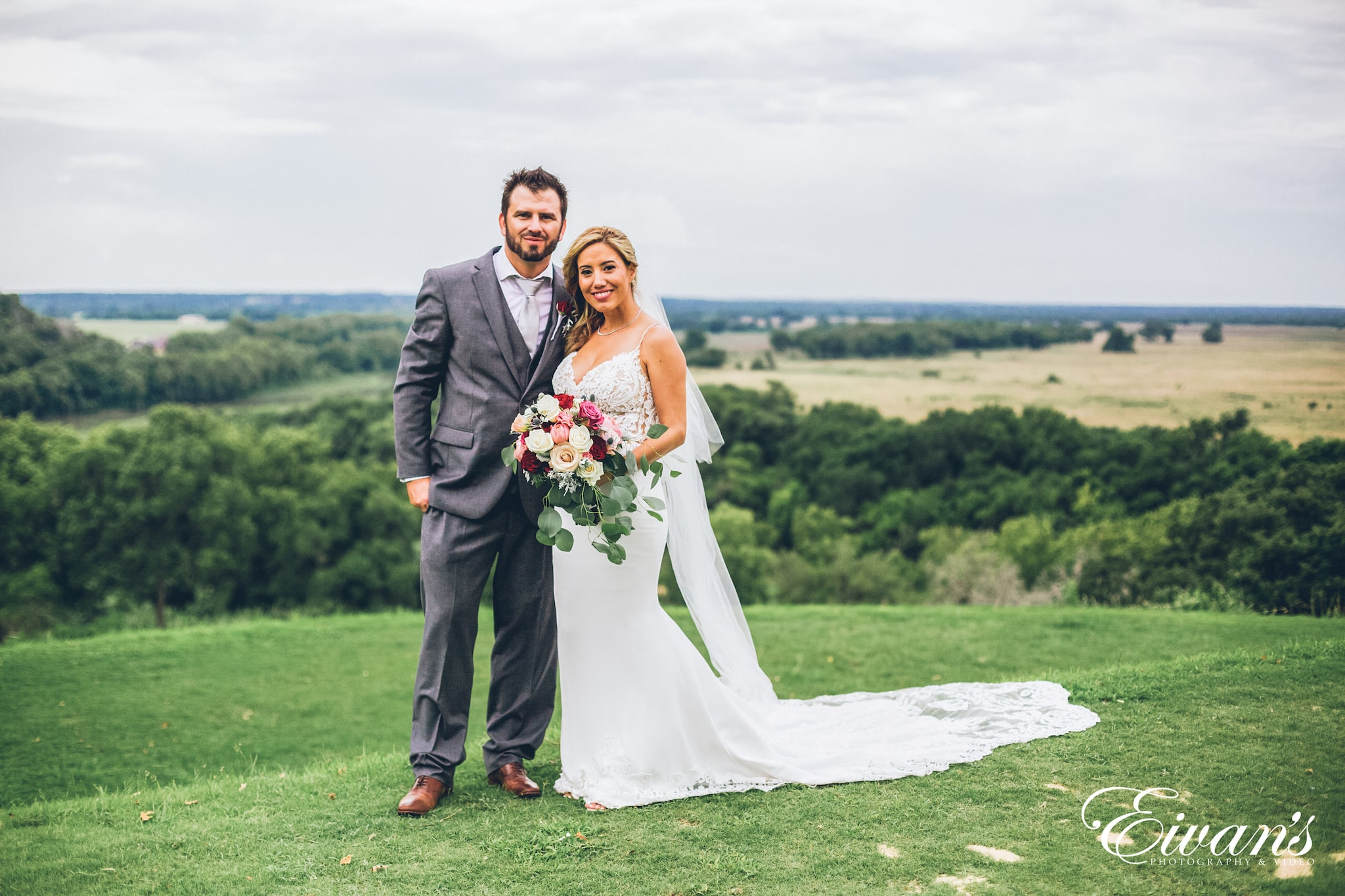 man in black suit and woman in white wedding dress holding bouquet standing on green grass
