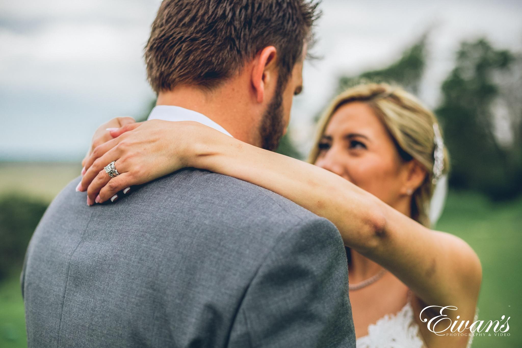 man in black suit jacket kissing woman in white dress