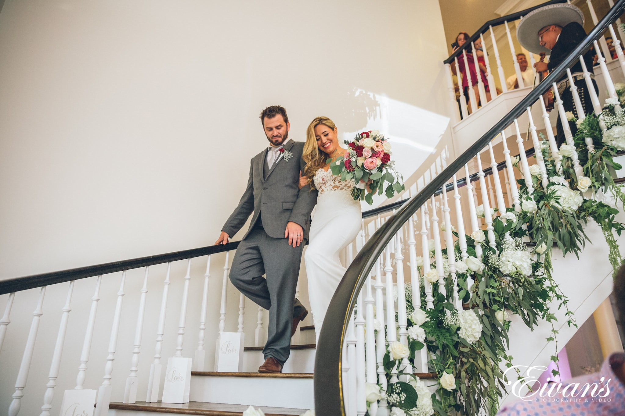 man in gray suit and woman in white wedding dress standing on staircase