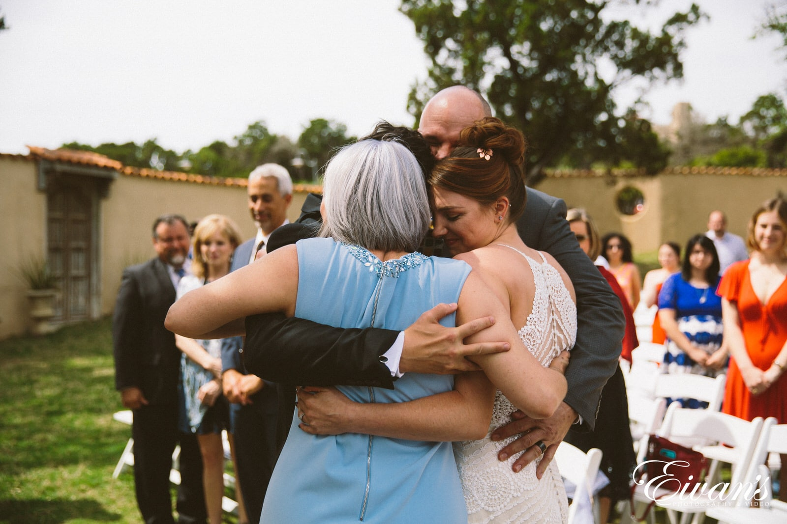 woman in white sleeveless dress hugging woman in black dress