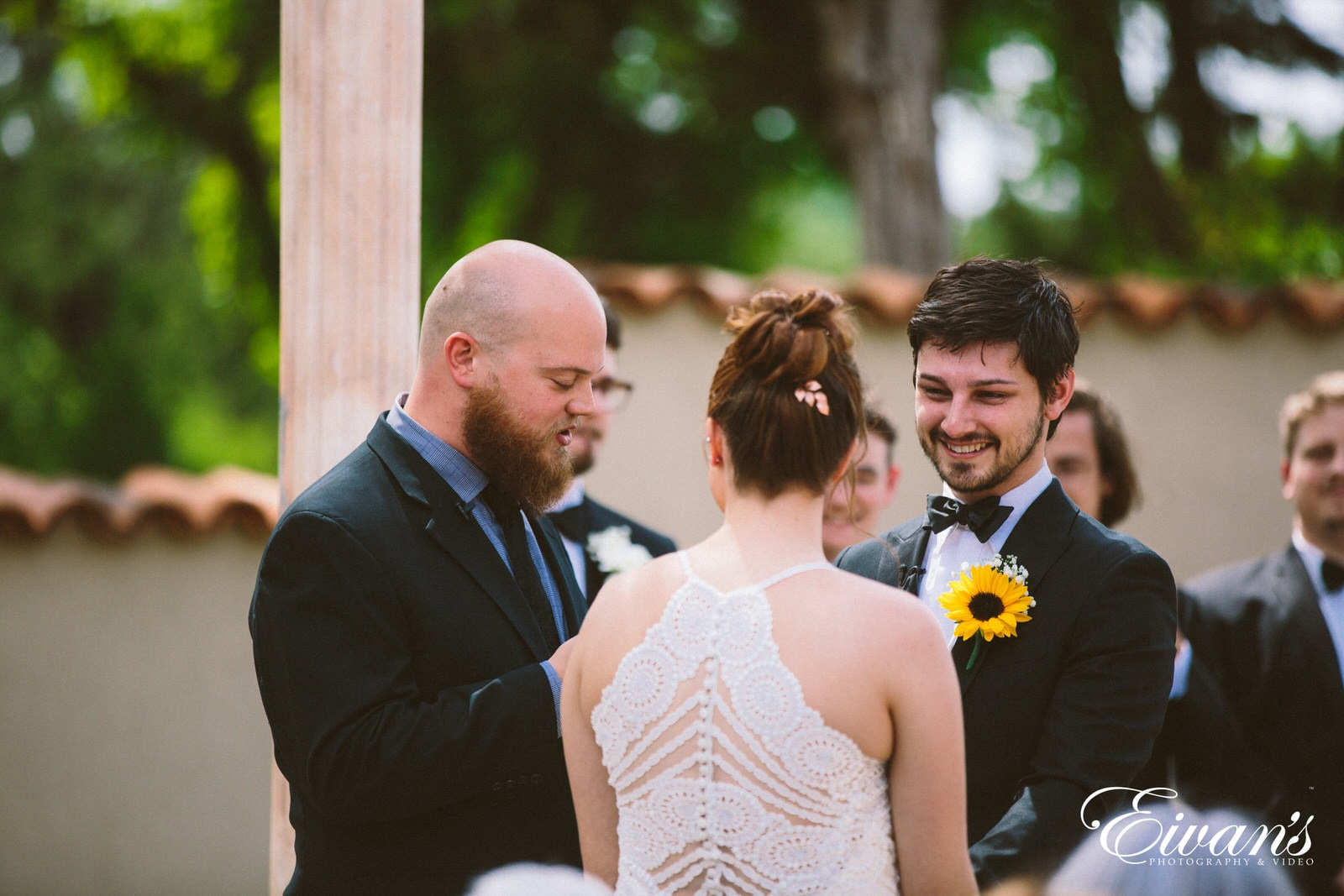man in black suit jacket and woman in white floral lace wedding dress