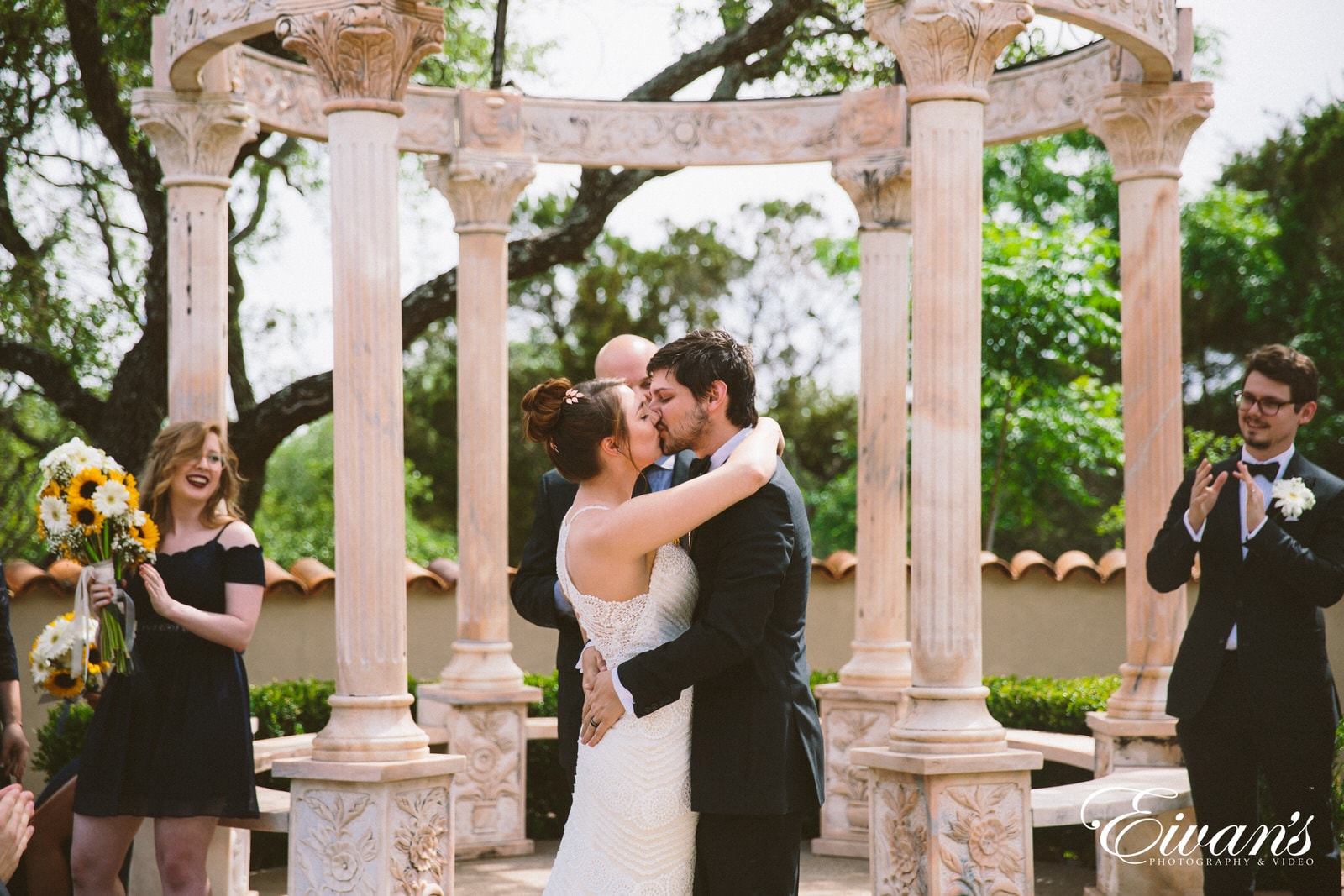 man and woman kissing under arch during daytime