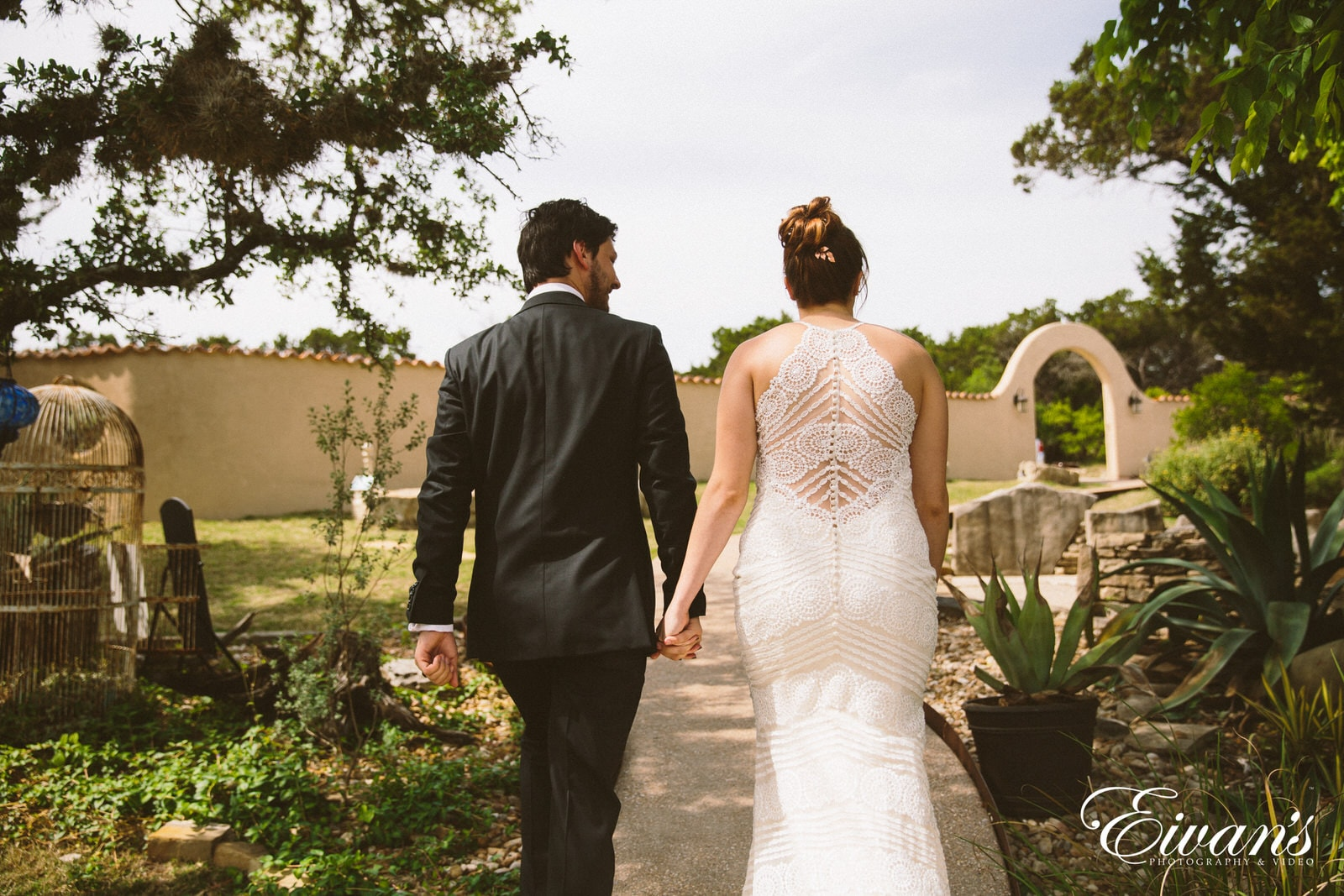 man in black suit and woman in white wedding dress walking on green grass field during
