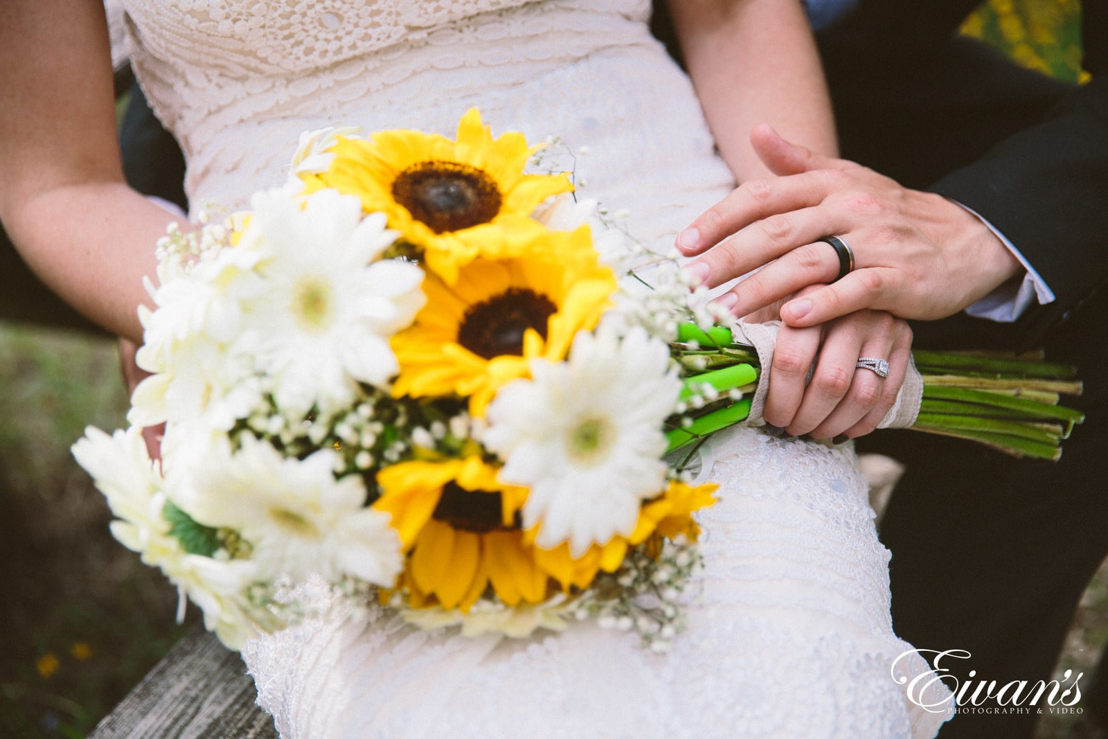 woman in white lace dress holding white and yellow flower bouquet
