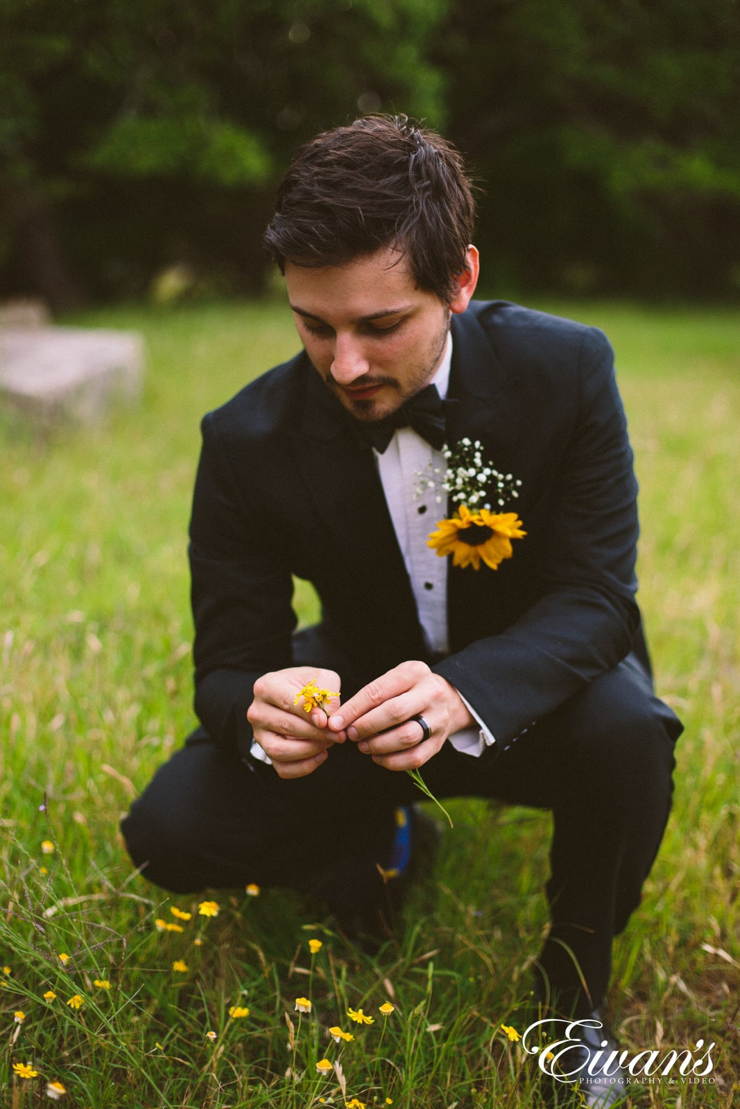 man in a black suit in a field of grass and yellow flowers