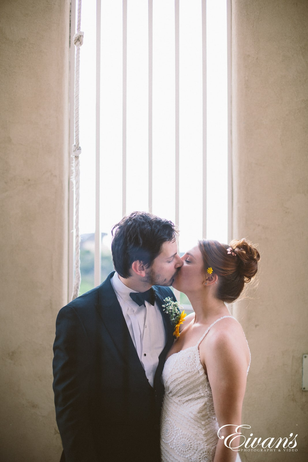 man in black suit kissing woman in white sleeveless dress